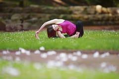 Giovane donna che fa gli esercizi di yoga nel prato inglese del parco Fotografia Stock