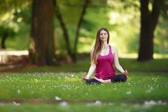 Giovane donna che fa gli esercizi di yoga nel prato inglese del parco Fotografia Stock Libera da Diritti