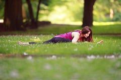 Giovane donna che fa gli esercizi di yoga nel prato inglese del parco Fotografie Stock Libere da Diritti