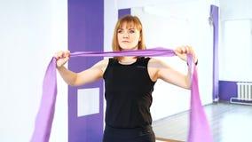 Giovane donna che fa gli esercizi per i muscoli di sviluppo delle mani, indietro ed addominale archivi video
