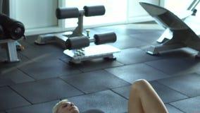 Giovane donna che fa gli esercizi per le natiche in palestra video d archivio