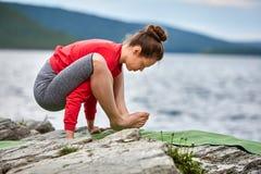 Giovane donna che fa l'equilibrio del braccio di posa di yoga sul grande fiume vicino di pietra Fotografia Stock