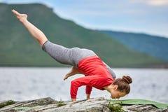 Giovane donna che fa l'equilibrio del braccio di posa di yoga sul grande fiume vicino di pietra Fotografie Stock
