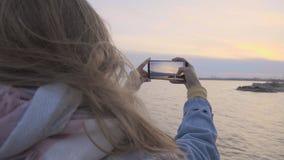 Giovane donna che fa la foto della spiaggia di tramonto al telefono video d archivio