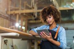 Giovane donna che fa lavorazione del legno in un'officina Fotografia Stock
