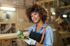 Giovane donna che fa lavorazione del legno in un'officina Immagini Stock Libere da Diritti