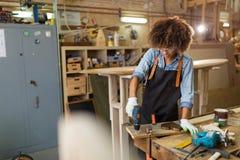 Giovane donna che fa lavorazione del legno in un'officina Immagini Stock
