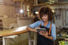 Giovane donna che fa lavorazione del legno in un'officina Immagine Stock