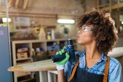 Giovane donna che fa lavorazione del legno in un'officina Fotografie Stock