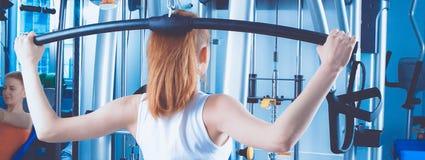 Giovane donna che fa le esercitazioni di forma fisica con l'espansore Fotografia Stock