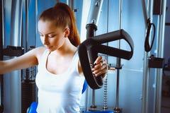 Giovane donna che fa le esercitazioni di forma fisica con l'espansore Fotografie Stock Libere da Diritti