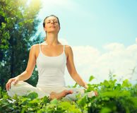 Giovane donna che fa le esercitazioni di yoga Immagine Stock