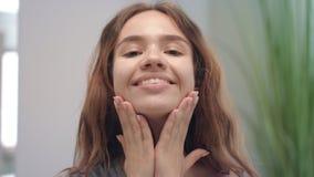 Giovane donna che fa massaggio della pelle sullo specchio anteriore del mento e del fronte in bagno archivi video