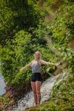 Giovane donna che fa posizione di yoga vicino ad una cascata fotografia stock