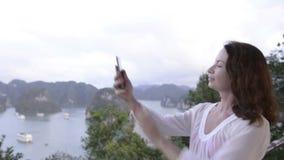 Giovane donna che fa selfie sulla cima della collina con il fondo delle isole e del mare
