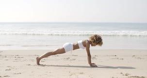 Giovane donna che fa Spinta-UPS sulla spiaggia video d archivio