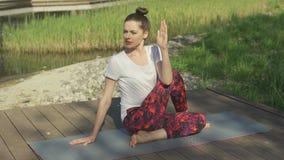 Giovane donna che fa torsione di yoga in parco video d archivio