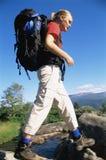 Giovane donna che fa un'escursione attraverso un fiume Fotografia Stock Libera da Diritti