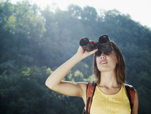 Giovane donna che fa un'escursione con il binocolo fotografie stock