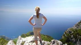 Giovane donna che fa un'escursione in montagne sopra il movimento lento della costa di Amalfi video d archivio