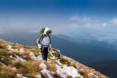 Giovane donna che fa un'escursione nelle montagne Immagine Stock