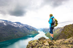 Giovane donna che fa un'escursione su Besseggen La ragazza felice gode di bello lago e di buon tempo in Norvegia immagine stock