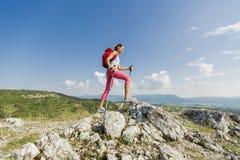 Giovane donna che fa un'escursione sulla montagna immagine stock