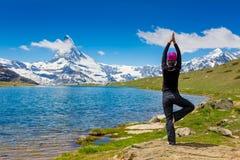 Giovane donna che fa una posa di yoga per equilibrio ed allungare Immagini Stock