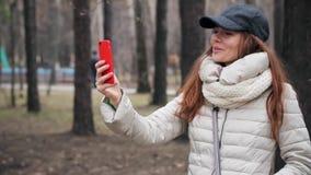 Giovane donna che fa una video chiamata con il suo smartphone al parco archivi video