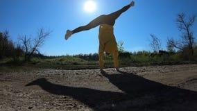 Giovane donna che fa vibrazione acrobatica con paesaggio su fondo stock footage