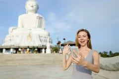 Giovane donna che fa video chiamata dallo smartphone e che mostra a Buddha statua bianca a Phuket immagini stock