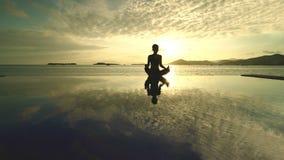 Giovane donna che fa yoga al tempo di tramonto immagini stock
