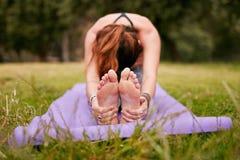 Giovane donna che fa yoga all'aperto sull'erba Fotografie Stock Libere da Diritti