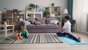 Giovane donna che fa yoga a casa mentre poco bambino che gioca con i blocchi di legno archivi video