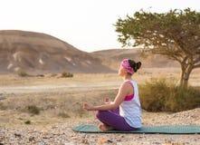 Giovane donna che fa yoga in deserto al tempo di alba Fotografie Stock Libere da Diritti