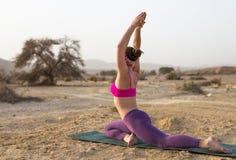 Giovane donna che fa yoga in deserto al tempo di alba Immagine Stock Libera da Diritti