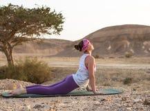 Giovane donna che fa yoga in deserto al tempo di alba Fotografia Stock