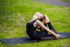 Giovane donna che fa yoga di ginnastica e che allunga nel parco della città sul tramonto Immagini Stock