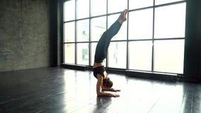 Giovane donna che fa yoga Yoga di pratica della donna in uno studio all'interno Yoga di pratica della giovane bella donna con la  archivi video