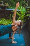 Giovane donna che fa yoga fuori nell'ambiente naturale Fotografia Stock
