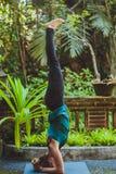 Giovane donna che fa yoga fuori nell'ambiente naturale Immagine Stock