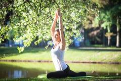 Giovane donna che fa yoga nel parco di mattina vicino al lago Fotografia Stock Libera da Diritti