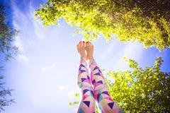 Giovane donna che fa yoga nel parco di mattina vicino al lago Fotografia Stock