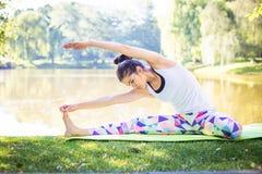Giovane donna che fa yoga nel parco di mattina vicino al lago Fotografie Stock