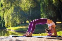 Giovane donna che fa yoga nella bella mattina vicino al lago Fotografie Stock Libere da Diritti