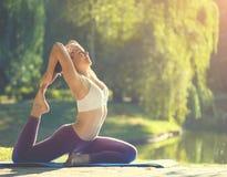 Giovane donna che fa yoga nella bella mattina vicino al lago Immagine Stock Libera da Diritti