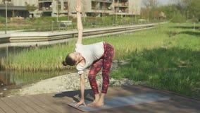 Giovane donna che fa yoga in sosta stock footage