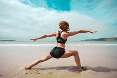 Giovane donna che fa yoga sulla spiaggia Fotografia Stock
