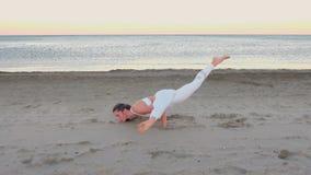 Giovane donna che fa yoga sulla spiaggia sabbiosa all'alba Posa dell'equilibrio stock footage