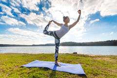 Giovane donna che fa yoga vicino al lago all'aperto, meditazione Forma fisica di sport ed esercitarsi in natura Tramonto di autun Immagini Stock